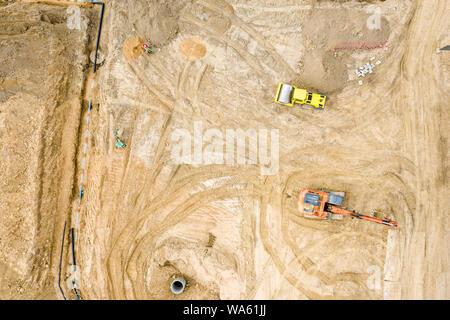 Vue de dessus du site de construction. les excavatrices et camions à benne de sable de chargement avant la construction de la route. photo aérienne Banque D'Images