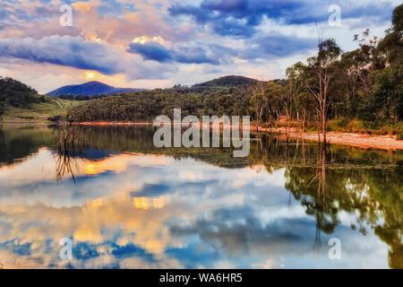 De soleil colorés sur le lac des eaux encore Lyell reflétant avec collines environnantes et de gommiers - la partie de NSW, Australie.