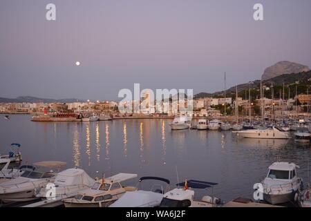 Pleine lune sur le port, avec des bateaux dans le port de plaisance dans l'avant-plan. Tôt le matin, la lumière. Banque D'Images