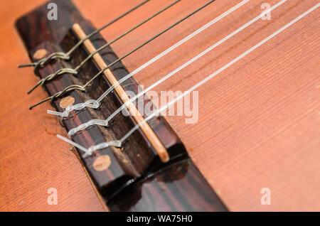 Pont d'une guitare acoustique. Cordes Nylon noué sur le pont de guitare. La profondeur de champ, les détails d'une vieille guitare acoustique, usé et poussiéreux. Banque D'Images