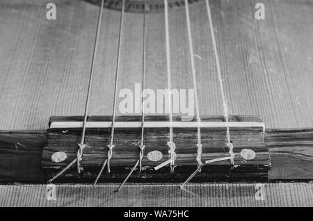 Pont d'une guitare acoustique. Cordes Nylon noué sur le pont de guitare. La profondeur de champ, les détails d'une vieille guitare acoustique, usé et poussiéreux. Un noir Banque D'Images