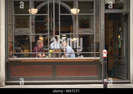 Londres, UK - août 2019. Avis de personnes ayant un café dans un café à travers la vitrine dans le centre de Londres. Banque D'Images