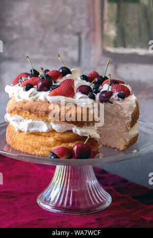 Belle angel food cake recouvert de crème fouettée et de fruits colorés frais Banque D'Images