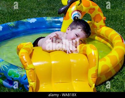 Jeune garçon posant dans sa piscine blow up Banque D'Images