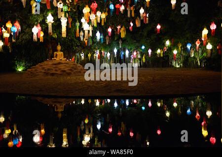 La superficie du lac avec statue de Bouddha assis sous un arbre de Bodhi à côté du viharn du temple bouddhique Wat Phan Tao qui est utilisé par les moines à la lumière des centaines de lampes à l'assemblée annuelle de Loy Krathong festival. Wat Chang, Chiang Mai, la province de Chiang Mai, Thaïlande, Asie du Sud Est Banque D'Images