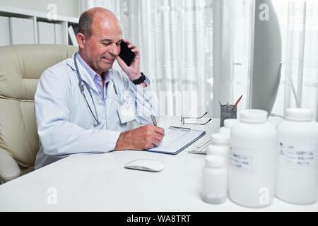 Cardiologue souriante et cardiogramme contrôle patient consultation sur le téléphone Banque D'Images