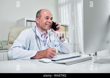 Smiling doctor la lecture des informations sur l'écran de l'ordinateur et prendre des notes lorsque vous parlez au téléphone avec patient Banque D'Images