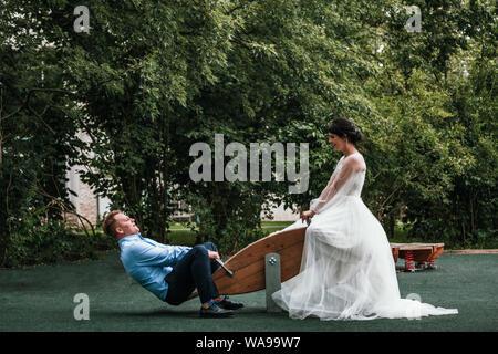 Jeunes mariés aiment passer du temps sur les balançoires. Mariage Concept, des jeunes mariés, nouvelle famille, copie de l'espace. Banque D'Images