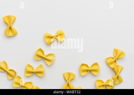 Matières premières italiennes pâtes farfalles multicolores sur fond blanc avec copie espace.pâtes colorées en forme de papillon. Concept de la cuisine italienne. Immersive. Banque D'Images