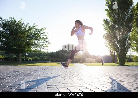 Vue de côté sportive woman running et la formation dans le parc en backli Banque D'Images