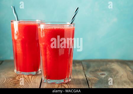 La sauce au melon d'eau avec citron vert et menthe, une boisson rafraîchissante d'été dans de grands verres sur fond bleu clair. Smoothie doux et froid avec espace de copie