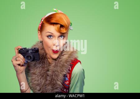 Belle jeune femme style pinup girl montre l'appareil photo numérique reflex numérique isolé sur fond vert mur. Closeup portrait photographe en utilisant Banque D'Images