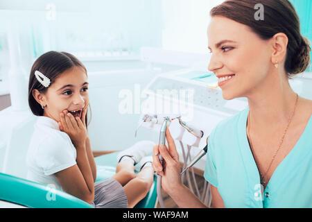 Dentiste pédiatrique avec son petit patient s'amusant à la clinique dentaire
