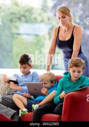 Mère veille sur ses enfants avec l'aide d'appareils Banque D'Images