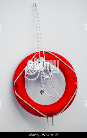 Les gardiens de la vie anneau rouge bouée de sauvetage suspendue sur mur blanc à la piscine. Bouée blanche avec un conseil sur mur blanc. Bouée rouge accroché sur mur blanc. Banque D'Images