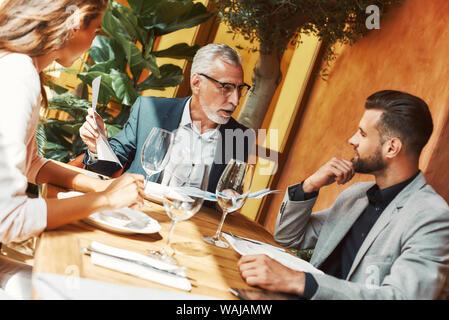 Portrait Portrait de trois collègues parler de leurs projets tout en restant assis dans un restaurant. Verres de vin sur la table. Plan horizontal