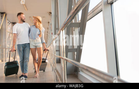 Les voyageurs couple walking in airport terminal walkway Banque D'Images