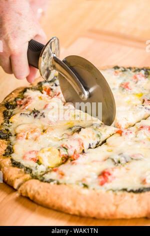 Femme à l'aide d'un cutter pour couper une pizza cuites au four fait maison, végétarien, pesto, multigrains, des pizzas à pâte épaisse. (MR) Banque D'Images