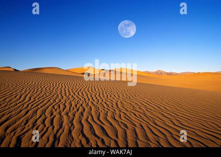 Pleine lune sur la lumière du soir sur dune motifs de la télévision Mesquite Sand Dunes, Death Valley National Park, California, USA. Banque D'Images