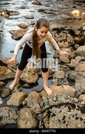 Olallie State Park, près de North Bend, Washington State, USA. Neuf ans, fille d'escalade sur des rochers dans la rivière Snoqualmie. (MR) Banque D'Images