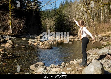 Olallie State Park, près de North Bend, Washington State, USA. Neuf ans, fille de jeter une pierre dans l'air. (MR) Banque D'Images