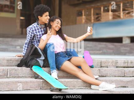 Couple posant pour l'appareil photo sur smartphone selfies Banque D'Images