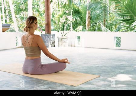 Woman Practicing Yoga avancée sur tapis organique. Série de postures de yoga. Arrière-plan de vie tropical. Concept