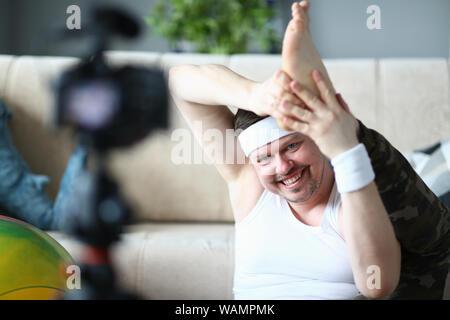 L'homme souriant à la caméra d'enregistrement Étirement des jambes