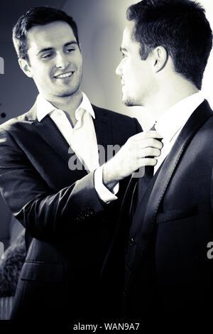Male couple gay, l'un regardant son partenaire qu'il corrige sa cravate pour lui. Banque D'Images