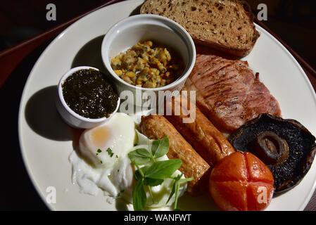 Un petit-déjeuner gallois, oeuf poché, laver les coques, pain, pain grillé, saucisses, bacon, tomate, champignons, cresson Banque D'Images
