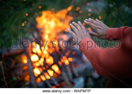 Jeune femme faisant feu en camping en plein air, dans une nature sauvage alpin - réchauffe ses mains près de l'incendie Banque D'Images