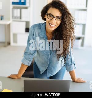 Happy friendly young businesswoman standing appuyée sur un bureau dans le bureau regardant la caméra avec un sourire chaleureux Banque D'Images