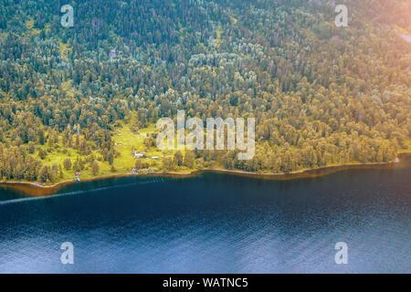 Petite maison indépendante dans l'Teletskoe Lake à l'Altaï près du lac entouré d'arbres verts sur une journée ensoleillée