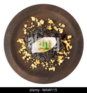 L'encre de seiche noire risotto au Calamar grillé sur plaque en bois ronde isolated on white Banque D'Images