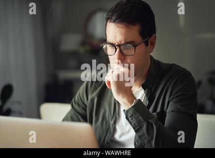 Portrait de l'accent man working on laptop at home