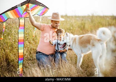 Portrait of a happy father and son holding kite air colorés en position assise avec chien sur le terrain pendant le coucher du soleil Banque D'Images