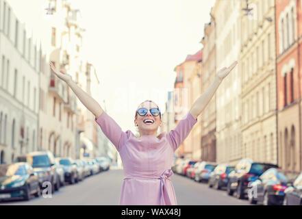 Happy woman se sentir libre à bras ouverts dans la ville lumière arrière profitant de locations