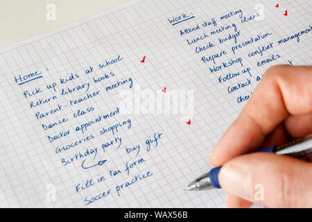 Liste des tâches. Concept d'équilibre travail/vie privée. Gros plan de la main d'un homme avec un stylo qui garde une liste manuscrite de tâches liées à la maison et au travail. Banque D'Images