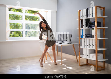Smiling young woman doing Stretching Exercice in Office Banque D'Images