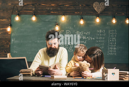 Père Fils, enseigne la lecture de livre, alors que mère jouer avec toy, tableau sur l'arrière-plan. Maman écoute garçon avec attention. Concept de Homeschooling Banque D'Images