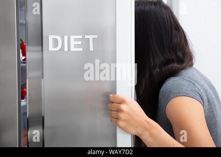 Portrait de femme à la recherche de nourriture de régime ouvert Réfrigérateur Banque D'Images