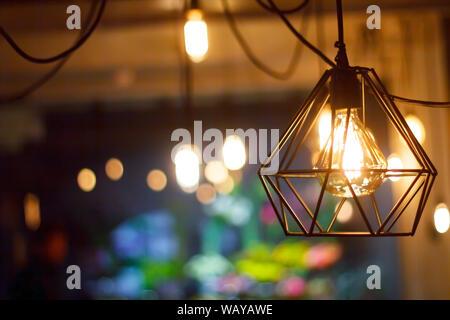 Close up vintage retro sphérique suspendu lumineux ampoule à incandescence d'Edison à l'encontre de l'arrière-plan flou d'autres feux, selective focus Banque D'Images