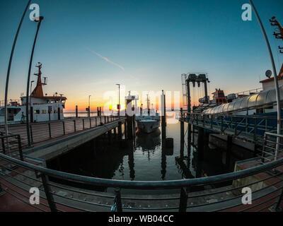 Langeoog Harbour avec les bateaux stationnés au lever du soleil Banque D'Images