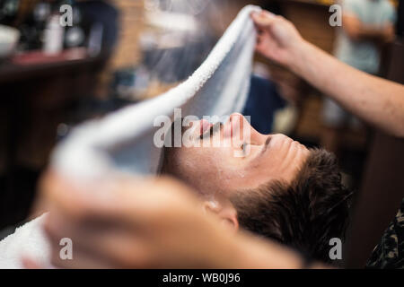 Coiffure couvre le visage d'un homme avec une serviette chaude. Rituel traditionnel de raser la barbe avec des compresses chaudes et froides dans un ancien style de coiffure. Cli Banque D'Images