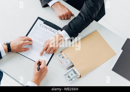 Portrait de l'homme tenir pen près de contrat et partenaire d'affaires mettre pot-in Pocket Banque D'Images
