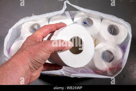Près d'un coup de frais généraux POV man's hands retrait d'un rouleau de papier toilette blanc frais à partir d'un emballage multiple du fournisseur. Banque D'Images