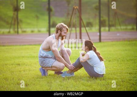 Remise en forme l'exercice abdominaux couple s'asseoir à l'extérieur dans l'herbe. Mettre en place les personnes qui travaillent à la formation. Woman doing abdominal crunches appuyez sur l'exercice avec Banque D'Images