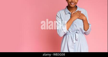 Reconnaissant african girl appuyant sur les mains à la poitrine Banque D'Images