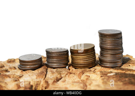 Quatre lignes de pièce sur souche d'arbre isolé sur fond blanc , pièces Pile dans un modèle graphique atteint , la croissance en montant de l'épargne Banque D'Images