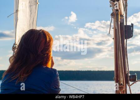Red-haired woman sur un voilier en admirant le coucher du soleil lointain ciel et rive boisée Banque D'Images